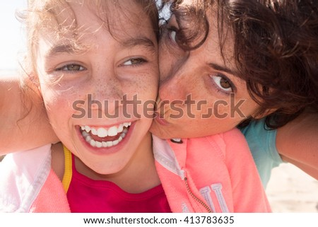 Mother and lovelydaughter smiling and cuddling