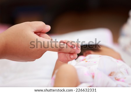 Mother and newborn baby girl holding hands. - stock photo