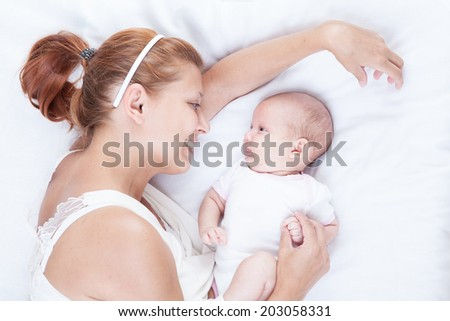 mother and newborn baby on white background - stock photo