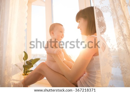 Mother and newborn in room near at the window - stock photo