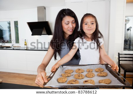 Mother and proud daughter holding sheet of cookies - stock photo