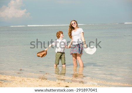 Mother and red haired son having family time on holidays waving with hats on  the beach. Travel, holiday, vacation concept  - stock photo