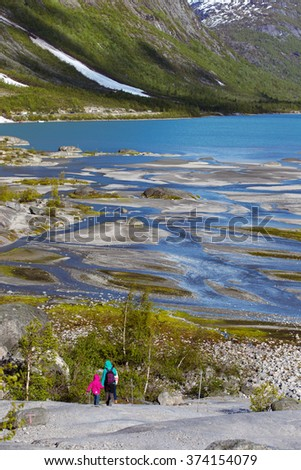 mother and sisters hiking on the lake with  mountains and the glacier Nigardsbreen at the background, view of the valley