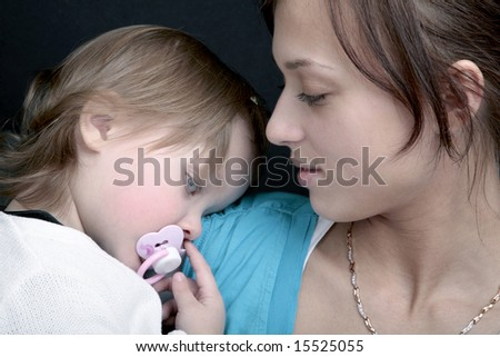 Mother and sleepy baby with pink dummy - stock photo