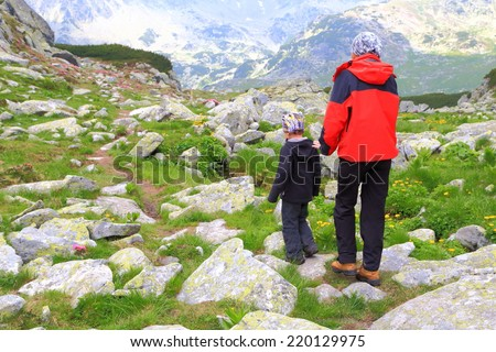 Mother and small boy on the mountain trail - stock photo