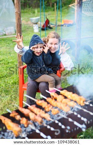 Mother and small  4 ears old daughter making faces during cooking meat - stock photo