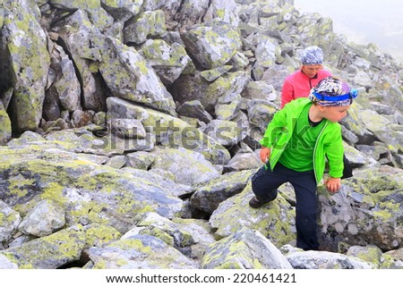 Mother and small kid on rocky mountain side - stock photo