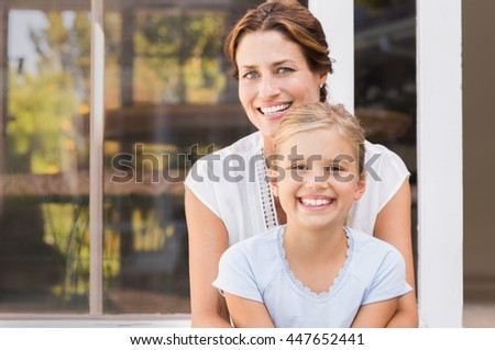 Mother and smiling daughter sitting outside the house. Happy mom and little girl enjoying in a summer day. Portrait of young mother embracing daughter sitting outside the house and looking at camera. - stock photo