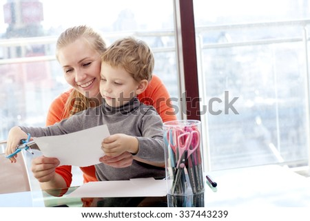 Mother and son are doing crafts - stock photo