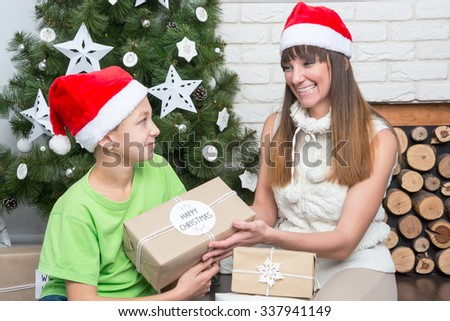 Mother and son are exchanged Christmas gifts at the Christmas tree. - stock photo