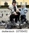 mother and son are feeding pigeons - stock photo