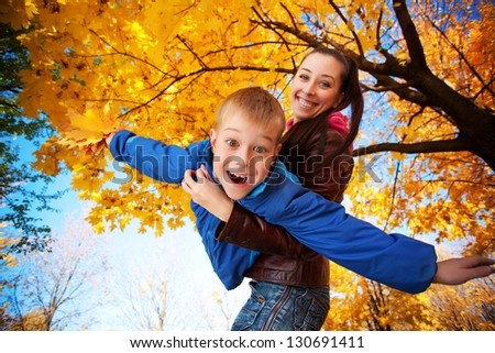 mother and son are playing in the autumn park