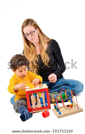 Mother and son are playing together as part of the creative children therapy. A therapist is working with little child. Didactic therapeutic toys for autism.   - stock photo