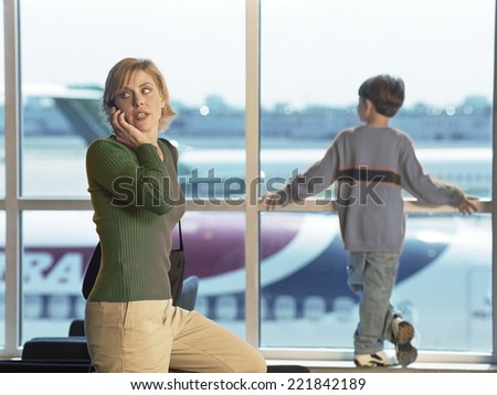 Mother and son at airport - stock photo