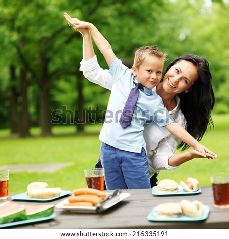 mother and son at picnic in park - stock photo