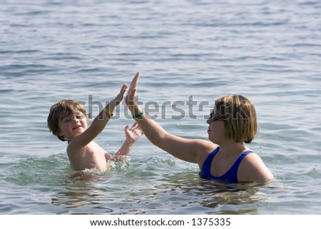Mother and son at the beach playing in the water - stock photo