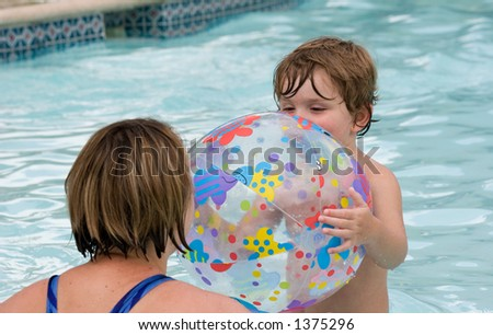 Mother and son at the pool playing in the water - stock photo