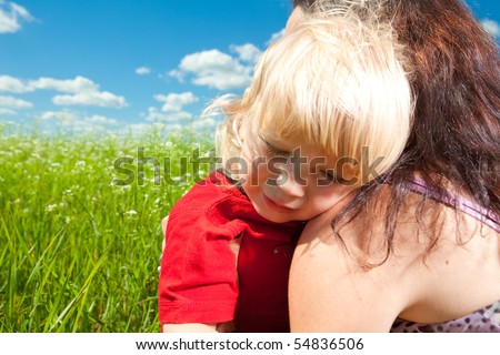 Mother and Son. Baby crying on the shoulder of mom - stock photo
