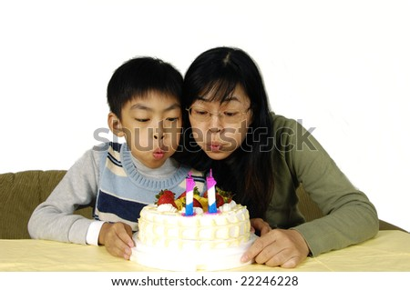 Mother and son blowing out candles - stock photo