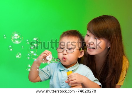 Mother and son blowing soap bubbles with Chinese appearance on green background - stock photo