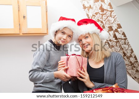 Mother and Son, both wearing red santa hats and having Christmas presents