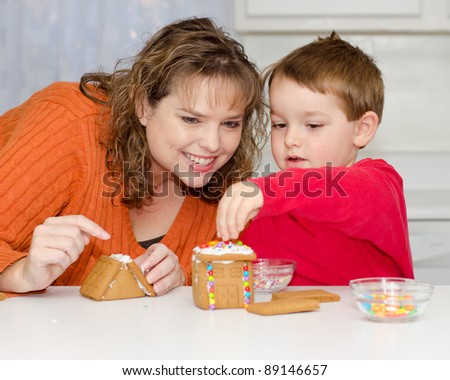 Mother and son build gingerbread house for Christmas - stock photo