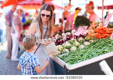 Mother and son buying green peas at market - stock photo