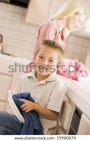 Mother And Son Cleaning Dishes - stock photo