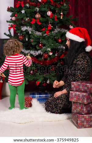 Mother and son decorating Christmas tree in their home