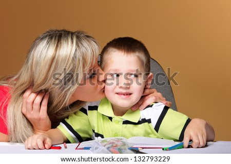 mother and son drawing together, mom helping with homework, kissing on cheek orange background - stock photo