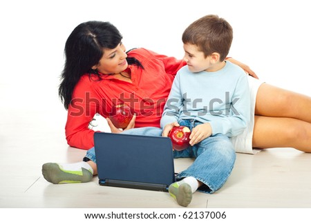 Mother and son eating apples and having some conversation together on floor in their home - stock photo