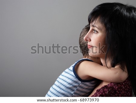 Mother and son embrace on gray gradient background - stock photo