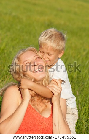 Mother and son embracing in a field