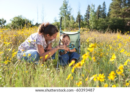 Mother and son enjoying late summer afternoon in nature. Shallow DOF, focus point is on boy's face. - stock photo