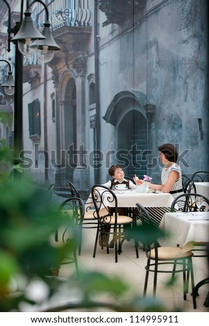 Mother and son enjoying meal sitting at cafe