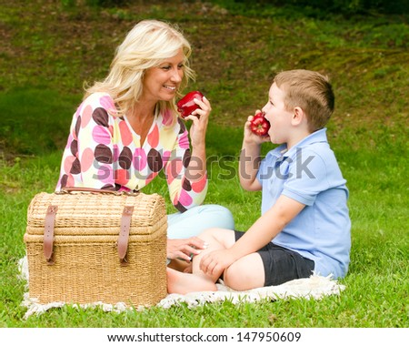 Mother and son enjoying picnic outdoors at park
