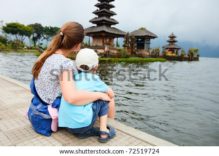 Mother and son enjoying views of beautiful Bali water temple at Bratan lake - stock photo