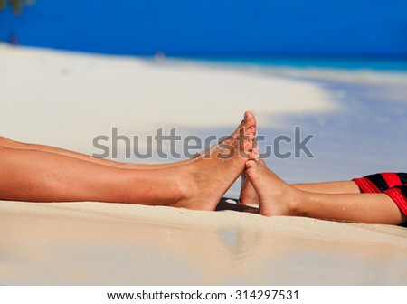 mother and son feet on summer beach, family beach vacation - stock photo