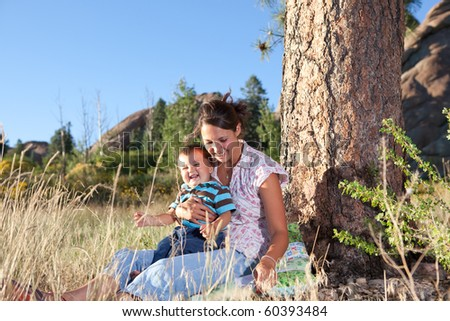 Mother and son goofing under a big pine tree in afternoon sun - stock photo