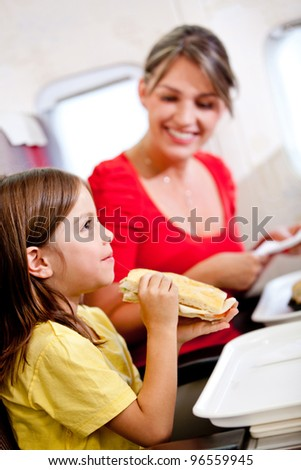 Mother and son having a meal in the airplane - stock photo