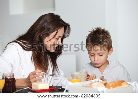 Mother and son having breakfast - stock photo