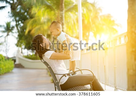 Mother and son having fun at outdoor in sunset during holidays. - stock photo