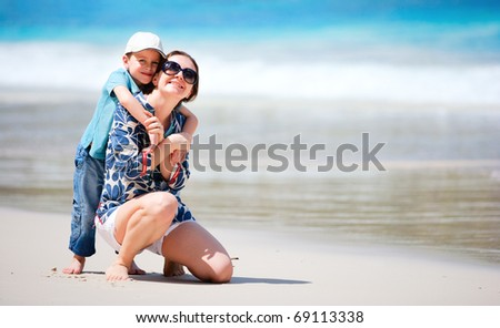 Mother and son having fun beach vacation - stock photo