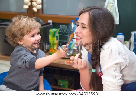 Mother and son having fun during breakfast. Little boy is smudging jam on mother's face. - stock photo