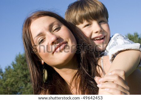 Mother and son having fun in a meadow - stock photo