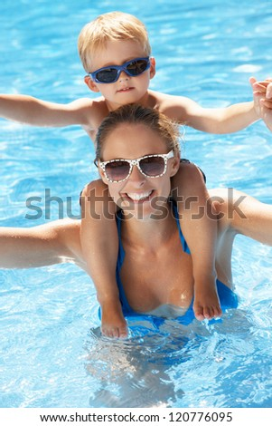Mother And Son Having Fun In Swimming Pool - stock photo
