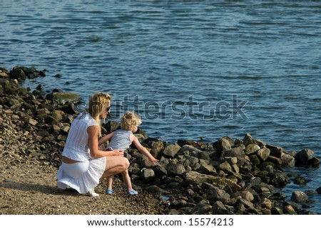 mother and son having fun on the waterfront - stock photo