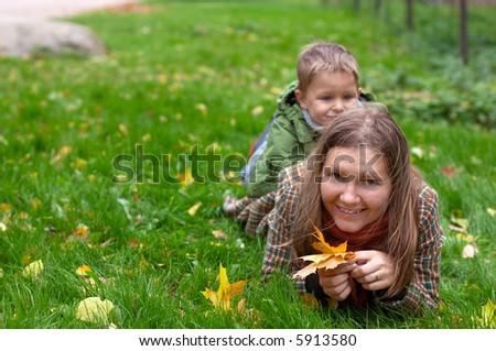 Mother and son having fun outdoors at sunny autumn day