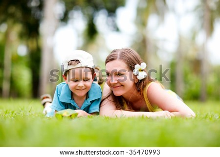 Mother and son having fun outdoors at sunny summer day