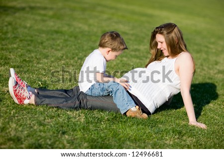 Mother and son having fun outdoors at sunny summer day. Little boy talking with unborn baby